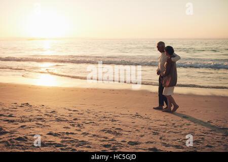 Schuss von älteres paar spazieren am Strand bei Sonnenuntergang. Senior Mann und ältere Frau bei einem Stockbild