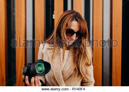 Porträt einer Frau mit Sonnenbrille im Besitz einer Kamera Stockbild