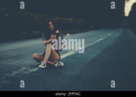 Reisende Frau mit Wunderkerzen auf der Straße Stockbild