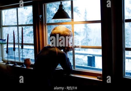 Junge aus dem Fenster schauen Stockbild