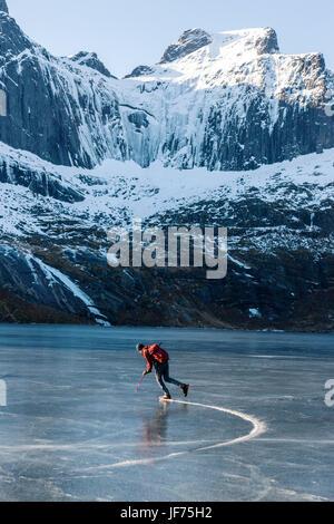 Mann, Schlittschuhlaufen auf dem zugefrorenen See Stockbild