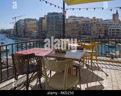 Spinola Bay in St. Julian's Malta eine geschützte Bucht mit Fischerbooten, Verkehr, Restaurants und Unterkünfte für Touristen Blick vom Cafe Kuba Stockbild