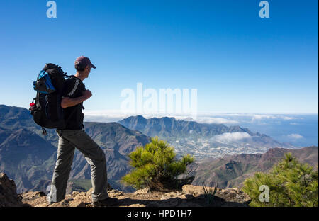 Ältere männliche Wanderer auf Alta Vista Berg auf Gran Canaria mit La Aldea de San Nicolas Dorf in Ferne. Stockbild