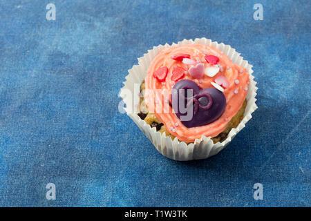 Detail der lustige Muffin mit lila Herz in blauen Hintergrund. Stockbild