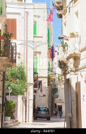 Molfetta, Apulien, Italien - 3. JUNI 2017 - Touristen zu Fuß durch eine Gasse in der Altstadt von Molfetta Stockbild
