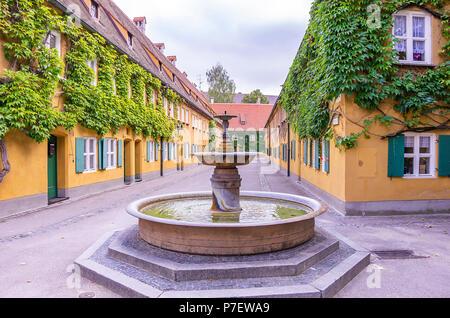 Augsburg, Bayern, Deutschland - 10. September 2015: Brunnen in der Herrengasse Gasse in die Fuggerei sozialen Wohnungsbau. Stockbild