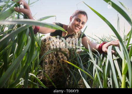 Lächelnde Frau Bauer stehen in ihrer Landwirtschaft Feld berühren das hohe Gras. Stockbild