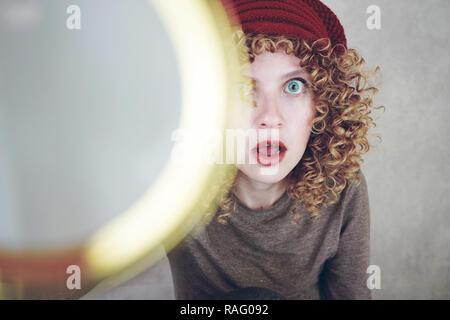 Nahaufnahme Porträt einer schönen und jungen lustige Frau mit blauen Augen und Lockige blonde Haare Untersuchung mit einer Lupe und Sie ist überrascht Stockbild