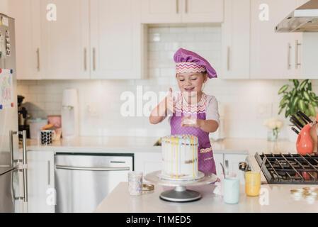 Lächelnde Mädchen dekorieren Kuchen in der Küche Stockbild