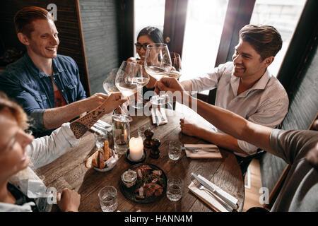 Gruppe von Männern und Frauen genießen Wein im Restaurant. Junge Freunde Toasten Wein im Café. Stockbild