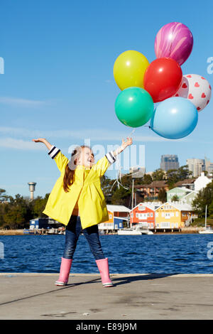 Mädchen in Regenmantel mit Luftballons Stockbild