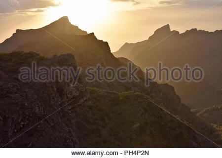 Sonne hinter vulkanischen Gipfeln der Teno Massiv (den Berg Macizo de Teno) im Nordwesten von Teneriffa Kanarische Inseln Spanien. Stockbild