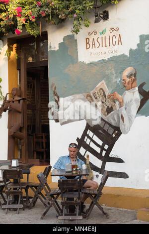 Ein Mann vor einem Café auf die bunten Straßen von Getsemani, Cartagena, Kolumbien Stockbild