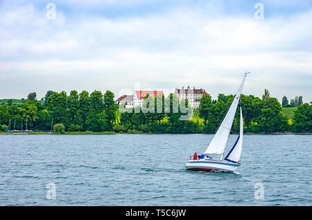 Am Bodensee, Deutschland - 09 Juni 2017 Immenstaad: Single Segelboot auf dem See vor dem Schloss Kirchberg mit Weinbergen. Stockbild
