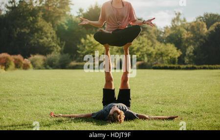 Starke junge Paar Acroyoga im Freien zu tun. Mann und Frau im Park paar Yoga-Übungen praktizieren. Stockbild