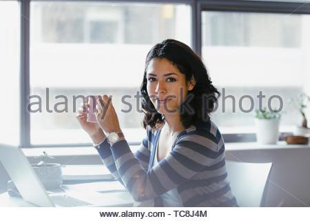 Portrait zuversichtlich Geschäftsfrau Kaffee trinken am Laptop im Büro Stockbild