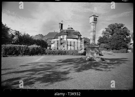 Kreisförmige Cottage, Hallen Straße, Blaise Hamlet, Bristol, c 1955 - c 1980. Außenansicht des Cottage entworfen von John Nash und George Repton und im Jahre 1812 erbaut. Das Ferienhaus befindet sich in der malerischen Stil und ist 1-stöckigen mit Zimmer im Dachgeschoss und hat eine 1-bay. Das Dach walm und strohgedeckten und die Wände sind Schutt mit Ziegel stapeln. Es ist ein Jahrhundert Erweiterung mit ziegeldach an der Rückseite des Hauses. Im Vordergrund ist das Grün mit Sonnenuhr und Pumpe aus dem Jahr 1815. Die Pumpe hat einen Löwenkopf und Wasserleitung auf der Basis einer Vierkantwelle, die mit einer quadratischen Kopf wi gekrönt wird Stockbild