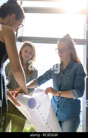 Kollegen aufrollen Charts nach dem Brainstorming Stockbild