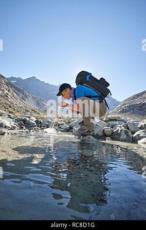 Wanderer das Trinken aus Pool, Mont Cervin, Matterhorn, Wallis, Schweiz Stockbild