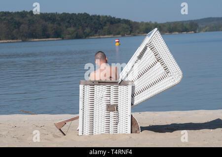19 April 2019, Berlin: ein Mann sitzt in einem Liegestuhl am Start der Badesaison am Wannsee Lido. Der Lido beginnt immer der Badesaison am Karfreitag. Der Eintritt ist frei bis Ostermontag. Foto: Paul Zinken/dpa Stockbild