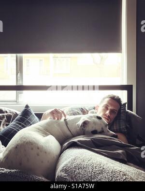 Mann im Bett mit Hund Stockbild