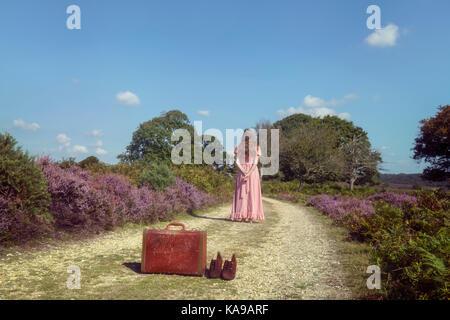 Eine Frau in einem lila Kleid ist ein Spaziergang durch die Heide, einem Koffer und Ihre Schuhe hinter Stockbild