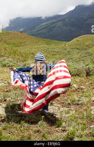 Mädchen in amerikanische Flagge im Feld gewickelt Stockbild