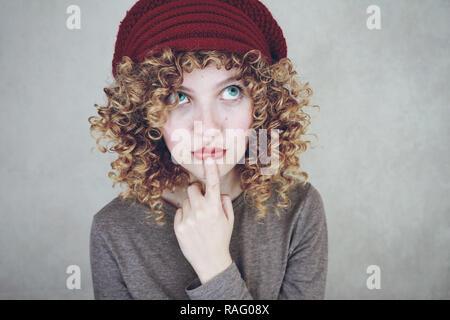 Nahaufnahme Porträt einer schönen und jungen Lustig nachdenklich Frau mit blauen Augen und Lockige blonde Haare denken und einen roten Wollmütze Stockbild
