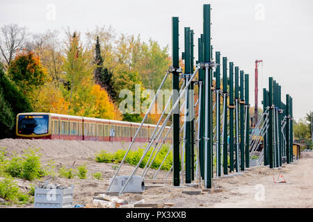Berlin, Germany. 19th Oct, 2018. Posts for noise barriers are located in the section between the Lichtenrade S-Bahn station and the Berlin-Brandenburg border along the future route of the Dresden Railway, while an S-Bahn passes by. (to 'Railway is driving the construction of the Dresden railway' from 20.10.2018) Credit: Christoph Soeder/dpa/Alamy Live News Stockbild