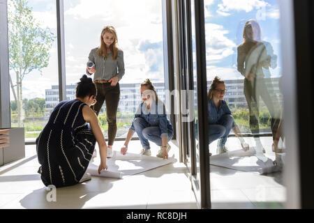 Kollegen aufrollen Diagramme auf dem Boden in hellem Sonnenlicht Stockbild