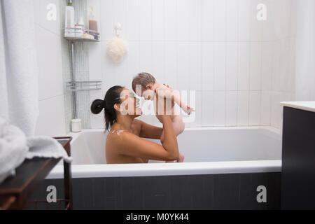 Die Mutter sitzt in der Badewanne Holding baby Sohn Stockbild