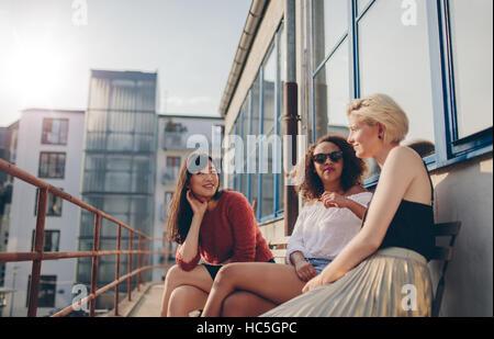 Drei jungen Freundinnen sitzen auf Balkon. Frauen im Freien entspannen und plaudern. Stockbild