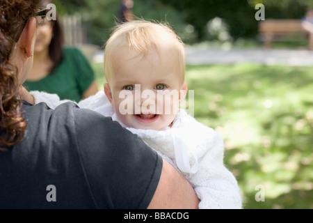 Eine Mutter trägt ihr Babymädchen über die Schulter-Blick Stockbild
