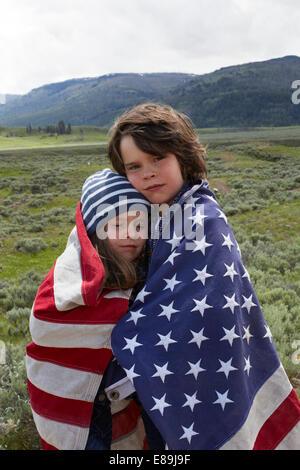 Bruder und Schwester gewickelt in amerikanische Flagge im Feld Stockbild