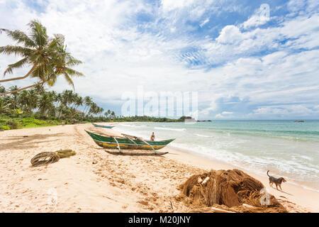 Balapitiya, Sri Lanka, Asien - eine Frau und ein Hund am Strand von Balapitiya Stockbild