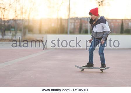 Volle Länge geschossen von einem Jungen auf einem Skateboard Stockbild