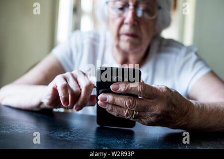 Nahaufnahme der älteren Frau an einem Tisch sitzen, mit Handy. Stockbild