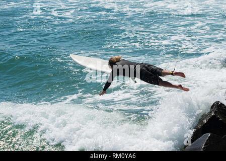 Ein Mann Tauchen im Meer mit einem Surfbrett. Stockbild