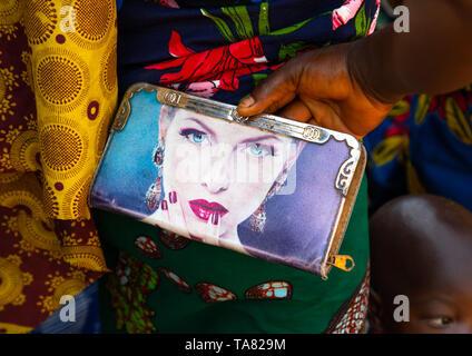 Afrikanische Frau, die eine Tasche mit dem Gesicht von einer weißen Frau, die auf ihm gedruckt, Bafing, Godoufouma, Elfenbeinküste Stockbild