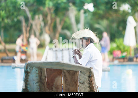 Ahungalla, Sri Lanka, Asien - ein Alter native Flute Player sitzen auf traditionelle Longboat Stockbild