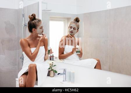 Junge Frau ihr Gesicht in Bad Gesichts Schlamm Tonerdemaske zuweisen. Schöne weibliche gewickelt Handtuch in Stockbild
