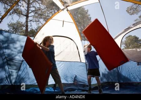 Zwei Jungs spielen mit aufblasbaren Matratzen in einem Zelt Stockbild