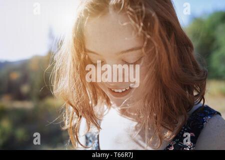 Lächelnde junge Frau mit sommersprossen nach unten schauen. Stockbild