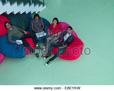 Lächelnde Geschäftsleute sitzen in Sitzsäcken Stockbild