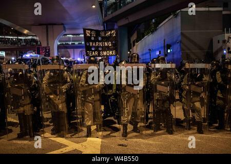Die Bereitschaftspolizei in Formation beim Reinigen von Connaught Road Show ein Banner Warnung vor Tränengas. Die Demonstranten mit den Hong Kong Polizei am Ende der bürgerlichen Menschenrechte vor März. Hongkong Demonstranten versammelten für ein weiteres Wochenende der Proteste gegen die umstrittene Auslieferung Rechnung und mit einer wachsenden Liste von Beschwerden, die der Aufrechterhaltung des Drucks auf Chief Executive Carrie Lam. Stockbild