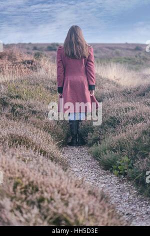 eine Frau in einem roten Mantel steht auf einem Pfad in die Heide im winter Stockbild