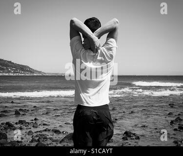 Mann von hinten am Strand Stockbild