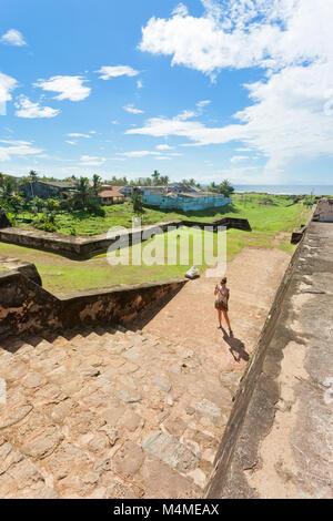 Sri Lanka, Asien, Galle - eine Frau, die in der mittelalterlichen Stadtmauer von Galle Stockbild
