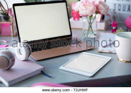 Rosa Pfingstrosen, Laptop und Bürobedarf auf Schreibtisch Stockbild