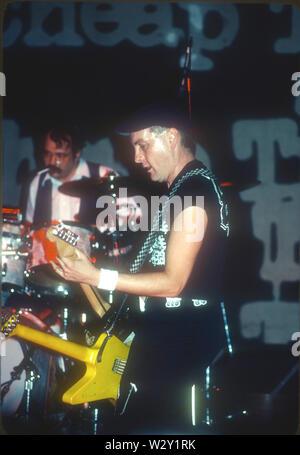 LOS ANGELES, Ca - 06 Dezember: Musiker Rick Nielsen (R) und ein Brötchen. E.Carlos von Cheap Trick in Konzert ca. 1982 im Hollywood Palladium in Los Angeles, Kalifornien. Stockbild